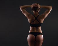 Muscular young woman. Standing on gray background Royalty Free Stock Image