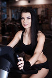 Muscular young woman wearing sportswear training on exercise bikes in gym. Intense cardio workout. Royalty Free Stock Photo
