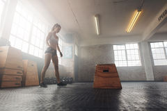 Muscular young woman working out with a box at crossfit gym stock photography