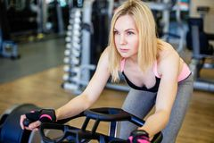 Muscular young woman working out on the exercise bike at the gym, intense cardio workout Royalty Free Stock Photo