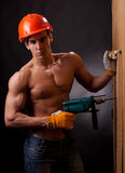Muscular young worker. In an orange helmet with an electric drill on a black background Stock Photos