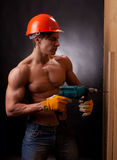 Muscular young worker. In an orange helmet with an electric drill on a black background Stock Images