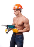Muscular young worker. In an orange helmet with an electric drill on a white background Stock Photos