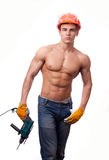 Muscular young worker. In an orange helmet with an electric drill on a white background Stock Photography