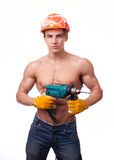Muscular young worker. In an orange helmet with an electric drill on a white background Royalty Free Stock Photos