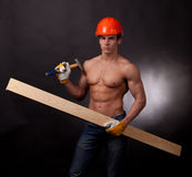 Muscular young worker. In an orange helmet with a hammer and board on a black background Royalty Free Stock Image