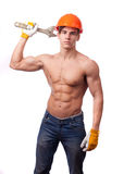 Muscular young worker. In an orange helmet and a wrench on a white background Royalty Free Stock Photo