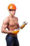 Muscular young worker. In an orange helmet and a wrench on a white background Royalty Free Stock Photos