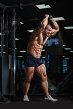 Muscularl athletic bodybuilder doing triceps exercises in gym. Muscularl athletic bodybuilder doing triceps exercises on block simulator in gym Royalty Free Stock Images