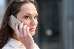Mused woman speaking by mobile. Portrait of female expressing thoughtfulness while telling by phone Royalty Free Stock Photo