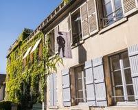 Musee de Montmartre exterior view, Paris, France. Entrance to the Musee de Montmartre and the Jardins Renoir, on the rue Cortot, Paris, France. Banner hangs in Royalty Free Stock Image