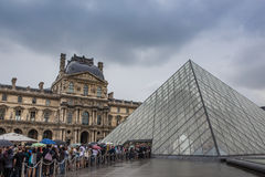 Musee du louvre. The entrance of Musee du louvre with the tourists at a rainy day in Paris , France Stock Photo