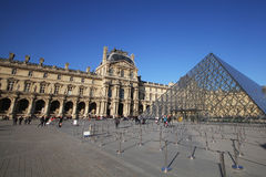 Musee du Louvre, the Illuminated attractive museum in nice sunny day, glassed pyramid in europe, Paris, France. Poster, wallpaper, backgrounds Stock Images