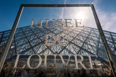 Musee Du Louvre Tecken framme av den stora glass pyramiden på Louvremuseet Royaltyfria Bilder