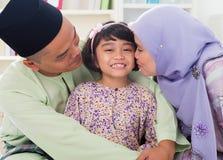 Muselmanen uppfostrar det kyssande barnet. Arkivbild