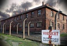 Museum Auschwitz - Birkenau. Warning sign high voltage. Barbed wire around a concentration camp. Stock Photo