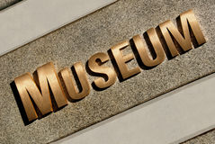 Museum Entrance Sign. Bronze Museum Entrance Sign on Granite Background In Morning Light Stock Photography