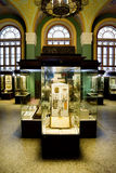 Museum exhibits of ancient relics in glass cases. Against big windows Stock Photography