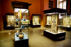 Museum exhibits of ancient relics in glass cases stock images