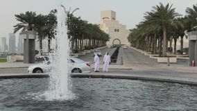 Museum of Islamic Art Doha. Doha, Qatar - February 16, 2019: two Arabs standing near fountain of Museum of Islamic Art with skyscrapers of West Bay skyline on stock footage