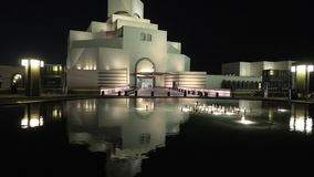 Museum of Islamic Art at night. Doha, Qatar - February 16, 2019: Museum of Islamic Art, along Corniche reflecting on fountain water in a night sky. Middle East stock footage