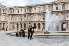 Museum workers and tourists near fountain at Louvre Royalty Free Stock Photography
