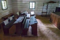 Museumexpositie van het klaslokaal met oude houten bureaus en onderwijsfaciliteiten stock afbeelding