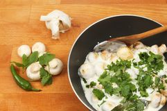 Mushroom balti and ingredients. Closeup of a mushroom balti in a pan with ingredients on a wooden worktop royalty free stock image