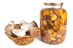 Mushroom in a basket. Glass jar of preserved mushroom isolated in white Royalty Free Stock Photography