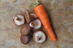 Mushroom and carrot. Natural organic carrot and mushroom on a vintage wooden background royalty free stock image