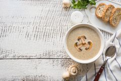 Mushroom champignon cream soup on white wooden board. View from above. Space for text. Delicious mushroom champignon cream soup on white wooden board.Top view royalty free stock photos