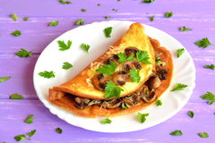 Mushroom and cheese omelet with herbs on a plate. Breakfast egg recipe. Omelette filling idea. Cooking scrambled eggs Royalty Free Stock Photos