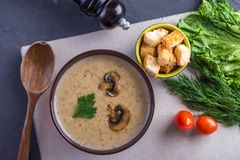 Mushroom cream soup in a brown plate on the table. Healthy autumn vegetarian traditional dish stock photos