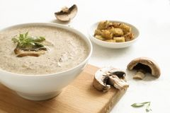 Mushroom cream soup with herb garnish and croutons on a light  background stock image