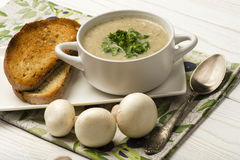 Mushroom cream soup  with roasted bread on the white wooden surface. Stock Photos