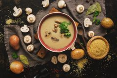 Mushroom cream soup on rustic background. Winter warming soup. Top view,overhead. Dark food photo.  royalty free stock photo