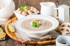 Mushroom cream soup. In a white bowl on wooden table Royalty Free Stock Image