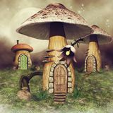 Mushroom fairy houses on a meadow. Three colorful mushroom fairy houses on a green meadow with flowers Royalty Free Stock Images