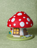 Mushroom Fantasy Cake. A children's birthday cake decorated as a cute fairy mushroom home with window and a door, and a little gnome taking a nap