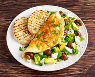 Mushroom, Feta Cheese egg Omelette witch Avocado, vegetables, lettuce, herbs and grilled bread. Stock Photos