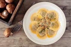 Mushroom filled ravioli pasta, overhead scene on wood. Mushroom filled ravioli pasta with nuts, parmesan and olive oil, overhead scene on a wood background Stock Image