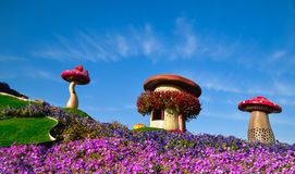 Mushroom houses at Miracle Garden, Dubai, UAE, 2016. Installation of mushroom houses on green grass field with flowers at Miracle Garden royalty free stock images
