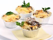 Mushroom julienne. Tasty mushroom julienne with spoon  on white Royalty Free Stock Photography