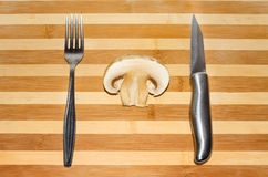 Mushroom with a knife and fork. Sliced mushroom with knife and fork on wooden table striped background Stock Images