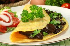 Mushroom omelet. An omelet stuffed with wild mushrooms and fresh salad royalty free stock photo
