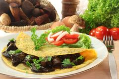 Mushroom omelet. An omelet stuffed with wild mushrooms and fresh salad stock images