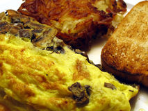Mushroom Omelet, Hash Browns, & Toast. This is a close up image of a mushroom omelet, hash browns, and toast stock photo