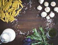 Mushroom pasta ingredients: penne, mushrooms, a jug of cream, pe Royalty Free Stock Photos