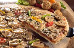 Mushroom pizza. A closed-up view of mushroom pizza with one slice being lifted from the wooden cutting board Stock Photography