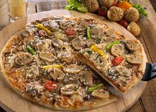 Mushroom pizza. A full size mushroom pizza with one slice being lifted from a wooden cutting board Royalty Free Stock Image